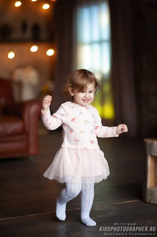 Девочка освоилась и играя бегает по фотостудии