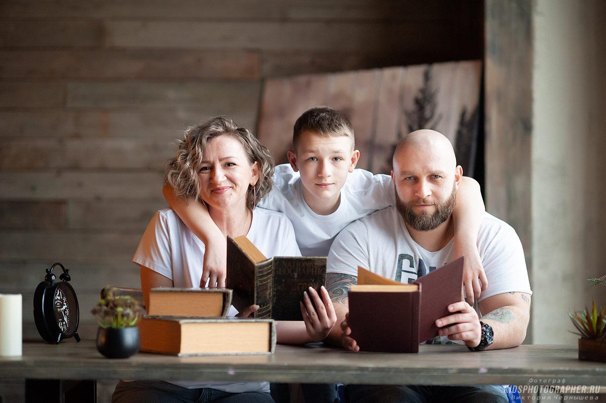 Семейное чтение книг за деревянным столом.
