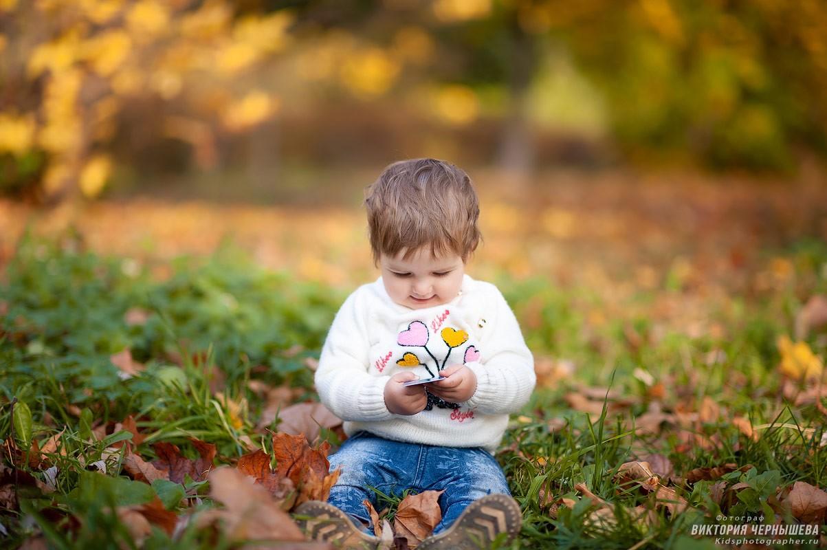 девочка сидит на земле осенью