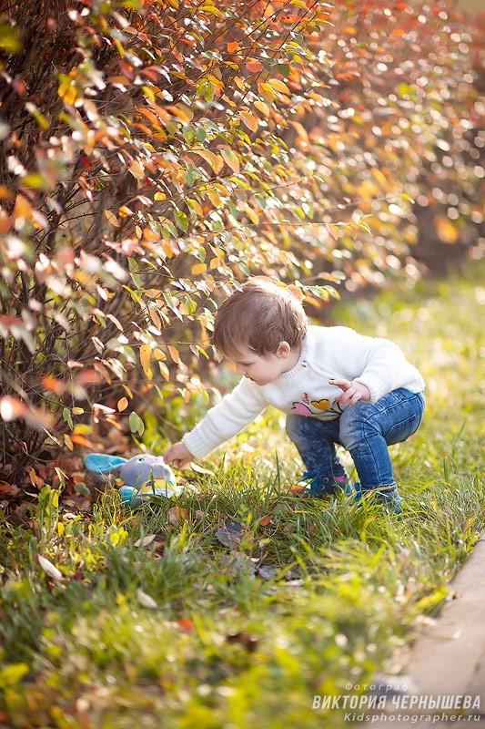 ребенок поднимает игрушку из кустов фото