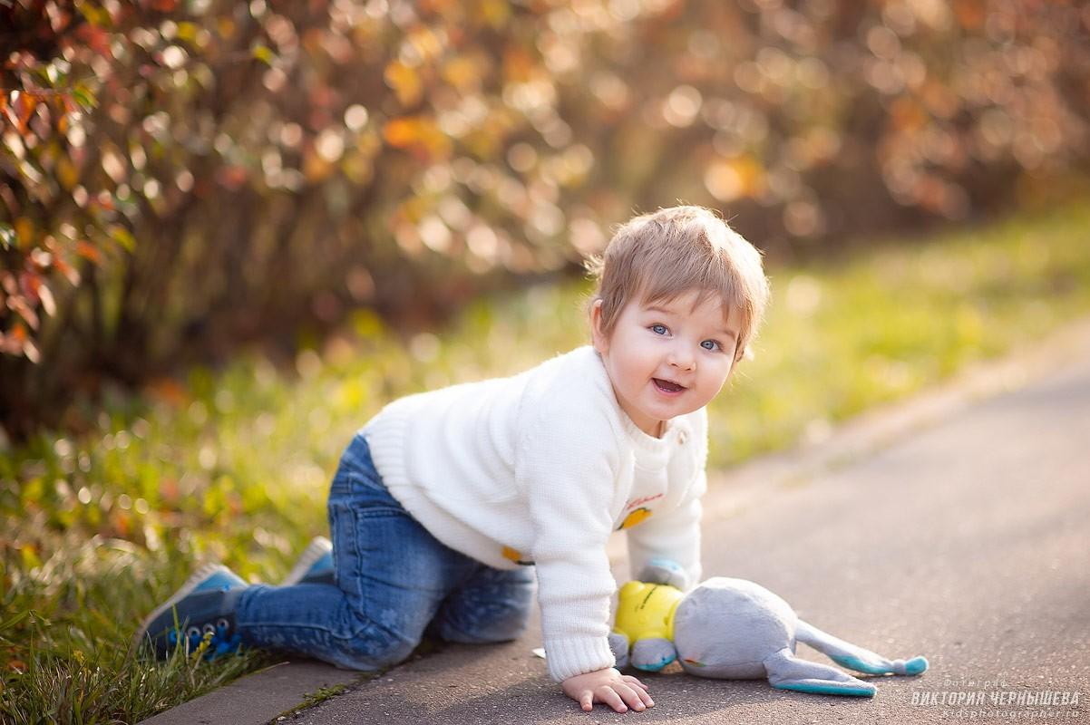 девочка ползает в осеннем парке фото