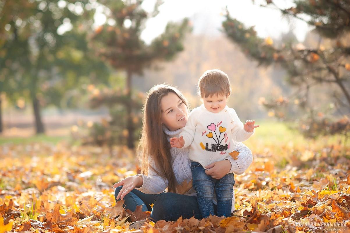 мама сидит на оранжевых кленовых листьях и обнимает дочку