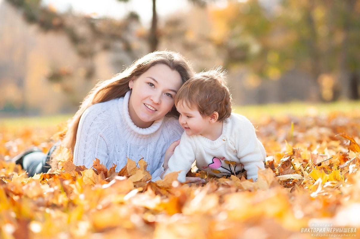 девушка с ребенком лежат на желтых листьях в парке