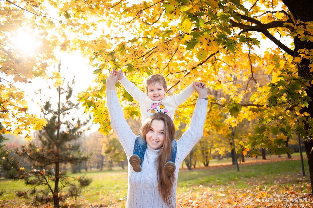 дочка сидит у мамы на шее на природе осенью фото